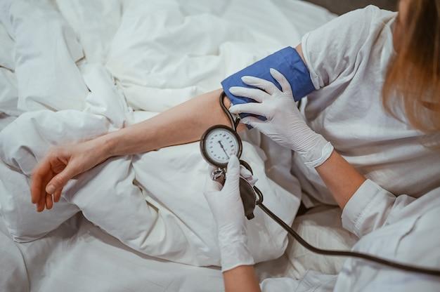 A enfermeira irreconhecível em luvas médicas mede a pressão arterial com um esfigmomanômetro. coronavírus (covid-19). primeiros sintomas. mulher doente de infecção viral da gripe em quarentena de isolamento em casa