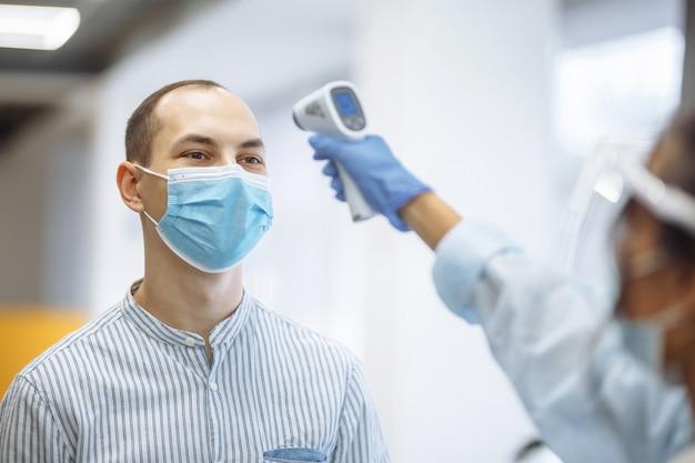 A enfermeira mede a temperatura de um paciente visitante do hospital com um termômetro sem contato. pessoas usando máscaras médicas protetoras. prevenção do coronavírus e conceito de saúde.