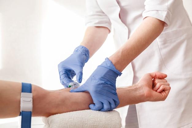 A enfermeira tira sangue de uma veia para teste