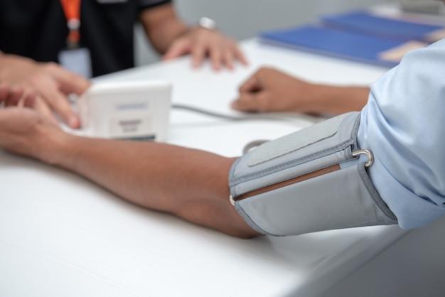 A enfermeira usa o medidor de pressão do braço do paciente.