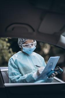 A enfermeira usa roupa de proteção e máscara durante o surto de covid19.