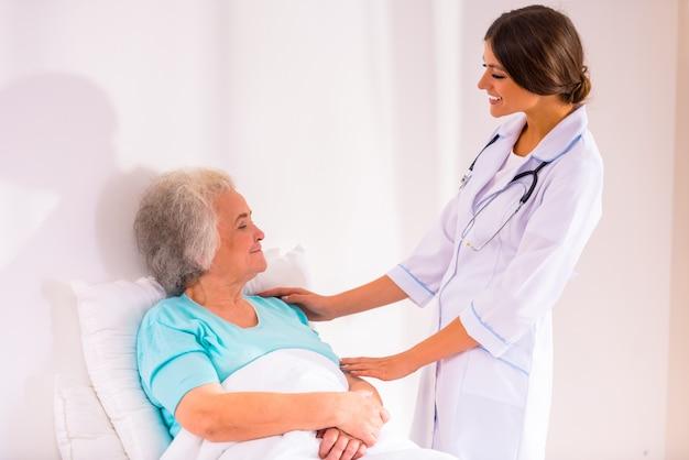 A enfermeira veio visitar a velha na cama.