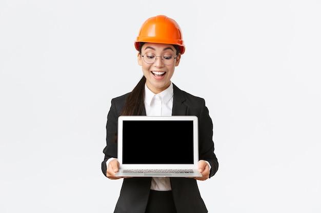 A engenheira-chefe asiática feliz e feliz, mostrando ótimos resultados empresariais para os investidores, usando capacete de segurança e terno de negócios, segurando um laptop e parecendo satisfeita com a tela do computador