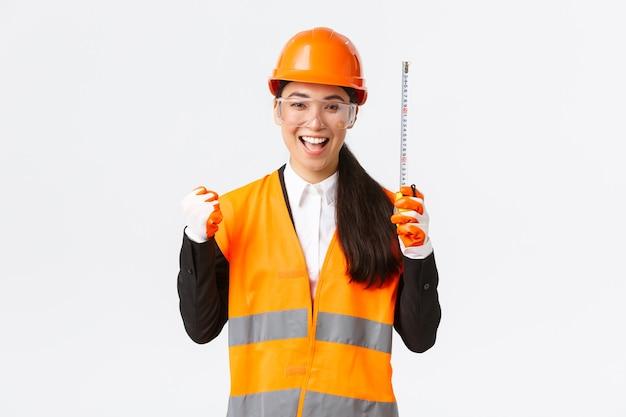 A engenheira de construção asiática vencedora de sucesso termina o trabalho, alcança ótimos resultados, empurra o punho alegre e diz sim, segurando uma fita métrica, o arquiteto fazendo as medidas corretas, regozijando-se