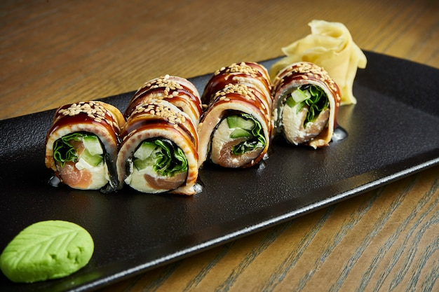 A enguia fresca rola com salmão, pepino e queijo de philadelphfia na placa preta na madeira. rolo de sushi japonês