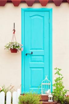 A entrada da casa, a porta de cor água com vaso de flores na parede