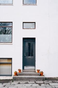 A entrada é feita por uma porta preta em um edifício moderno com janelas de diferentes tamanhos e flores