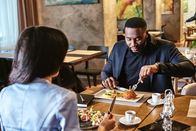 A equipa que come junta fica junta a dois colegas a almoçarem no foco do restaurante da empresa