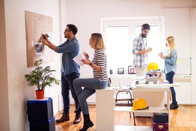 A equipe criativa trabalhadora está tentando debater novas idéias inovadoras conversando entre si, anotando-as no quadro marrom e em suas anotações no escritório