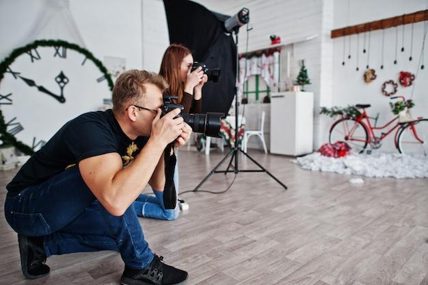 A equipe de dois fotógrafos atirando no estúdio. fotógrafo profissional no trabalho.
