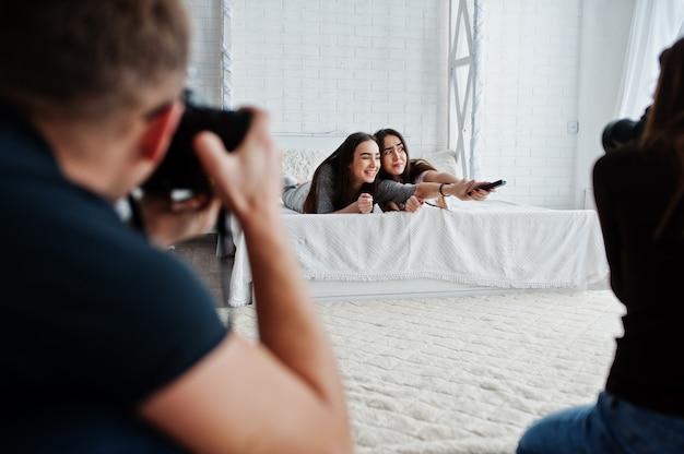 A equipe de dois fotógrafos fotografando gêmeos modela meninas enquanto clicam no controle remoto da tv no estúdio. fotógrafo profissional no trabalho.