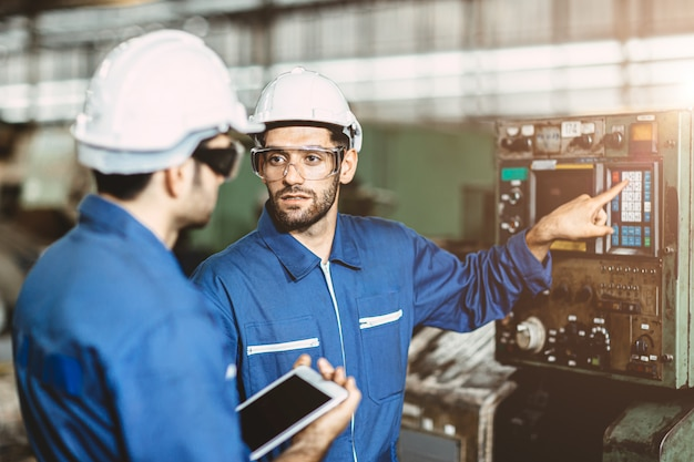 A equipe de engenheiros conversando em conjunto com a discussão ensina e aprende fornece educação técnica sobre o uso da máquina no local de trabalho da fábrica.