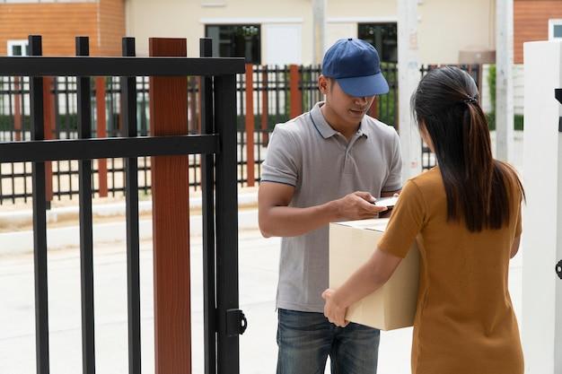 A equipe de entrega está enviando produtos para os clientes e usando smartphones para assinar produtos.