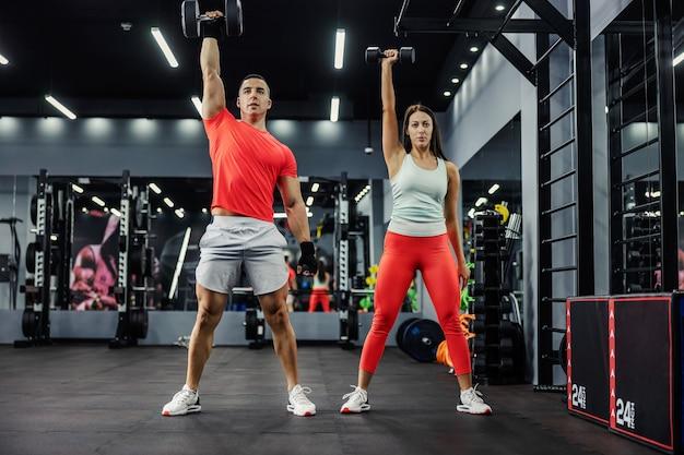 A equipe de fitness faz exercícios para os braços com pesos na academia de base preta