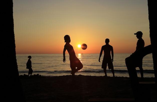 A equipe de futebol masculino, ensaios jogando futebol na praia do mar com o pôr do sol.