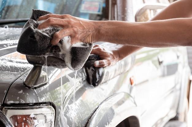 A equipe de lavagem de carros está usando uma esponja umedecida em água e sabão para limpar o carro.
