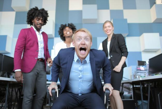A equipe de negócios engraçados lidera alegremente gritando após uma reunião produtiva com seus colegas multiétnicos