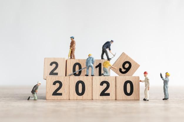 A equipe de trabalhador em miniatura cria o número 2020