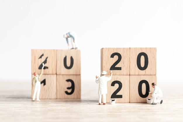 A equipe de trabalhador em miniatura pintou o número 2020 e remove o número 2019