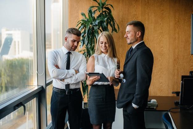 A equipe do escritório para discutir assuntos de negócios ao lado da janela. finança de negócios