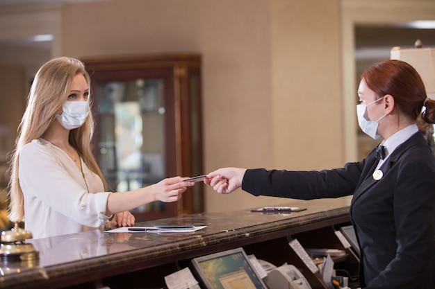 A equipe do hotel atende os hóspedes com máscaras médicas