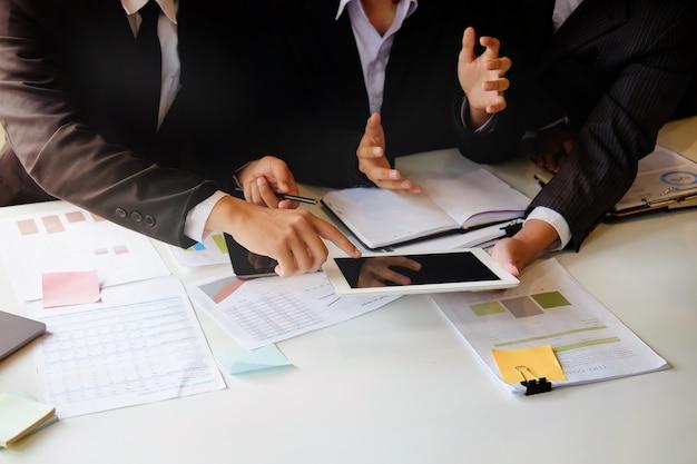 A equipe do negócio consulta e reunião com a foto ascendente próxima do tiro da tabuleta.