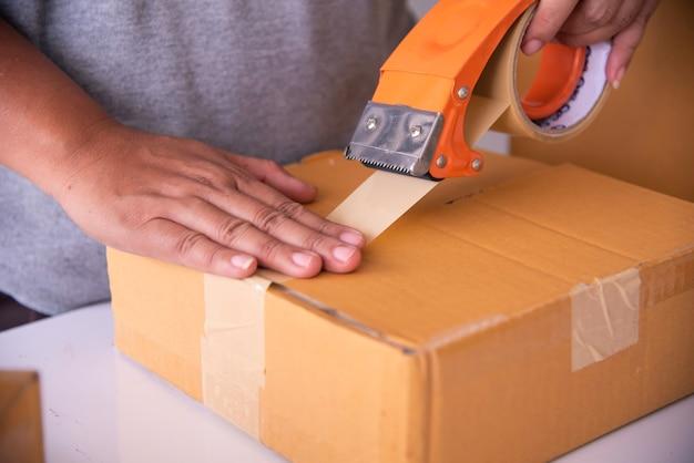 A equipe está usando a fita adesiva para embalar as mercadorias do pacote para o cliente.