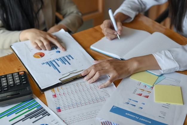 A equipe feminina do escritório resume o orçamento para a apresentação executiva anual.