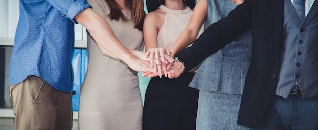 A equipe multiracial bem sucedida feliz do negócio que dá um fives alto gesticula enquanto riem e cheer seu sucesso.