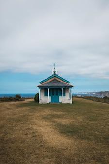 A ermita de la regalina rodeada pelo mar sob um céu nublado nas astúrias, espanha