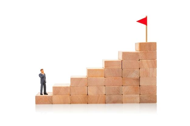 A escada da carreira é o símbolo do caminho para a meta. homem de terno está na bandeira da meta