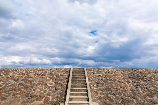 A escada para a represa é preenchida com pedra, céu nublado