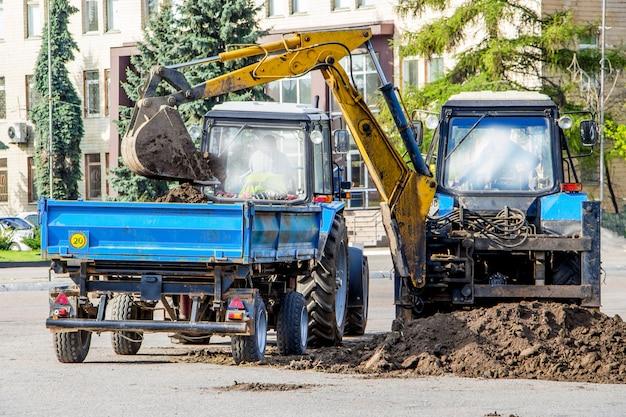 A escavadeira carrega a terra no reboque do trator