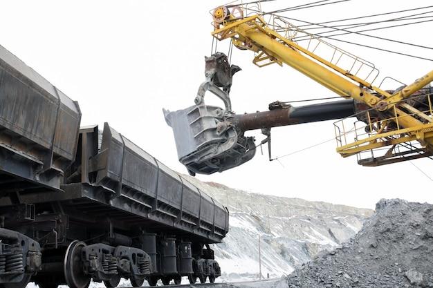 A escavadeira carrega as pedras nos carros.