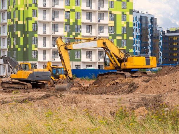 A escavadeira cava o terreno para a fundação e construção de novos edifícios.
