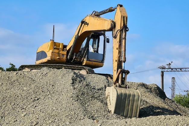 A escavadeira está em uma pilha de escombros contra o fundo do céu e das estruturas da ferrovia