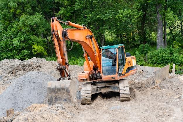 A escavadeira realiza trabalhos de escavação no canteiro de obras. trator amarelo cava o chão