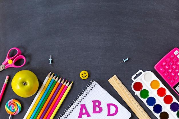 A escola colorida fornece matérias em um fundo de quadro preto
