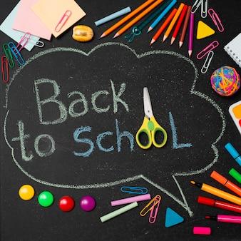 A escola multicolorida fornece lápis e uma nuvem desenhada com espaço de cópia para o texto