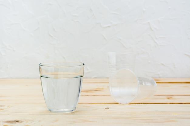 A escolha de um copo de vidro com água versus plástico descartável em uma mesa de madeira natural