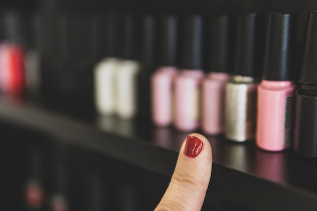 A escolha do esmalte. um dedo com uma unha pintada de vermelho aponta para os frascos de esmalte. muitas opções de esmaltes nas prateleiras da loja.