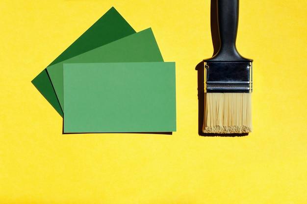 A escolha nova da escova e da pintura colore o molde no fundo amarelo com espaço da cópia.