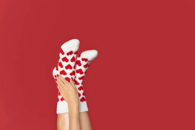 A escova acaricia suavemente os pés dos pés vestidos com meias quentes de lã com uma impressão brilhante de corações em um vermelho