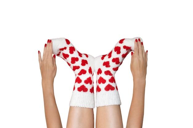 A escova acaricia suavemente os pés dos pés vestidos com meias quentes de lã com uma impressão brilhante de corações sobre um fundo vermelho.