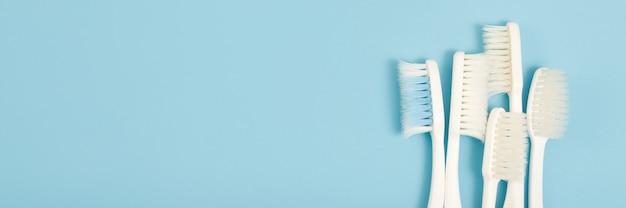 A escova de dentes velha usava uma variedade de cores vencidas (danificadas) no fundo azul. conceito usado para fabricação da indústria de saúde dentista profissional ou freqüentemente deve trocar sua escova de dentes.