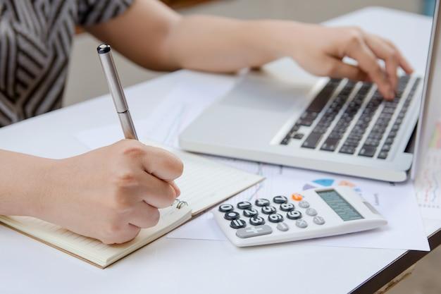 A escrita da mulher faz a nota e a utilização do escritório da finança do portátil em casa.