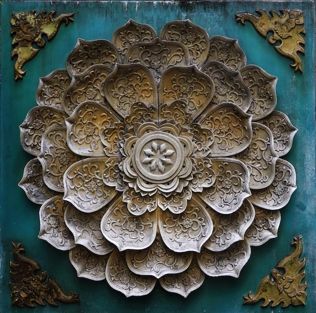 A escultura em pedra parece que as pétalas das flores estão decoradas.