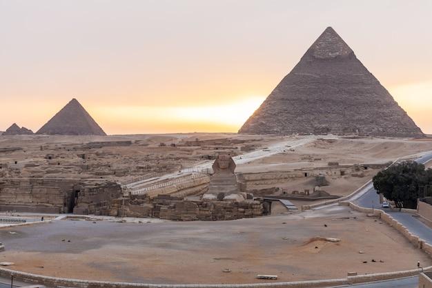 A esfinge, a pirâmide de khafre e a pirâmide de menkaure em gizé ao pôr do sol, egito.