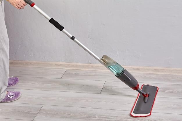 A esfregona de pulverização plana envolve a cabeça de microfibra para limpeza de pisos de madeira com gatilho de pulverização de água localizado na extremidade do cabo.