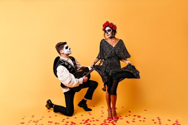 A esguia senhora mexicana dança e toca a barra do vestido ao som de uma serenata foto de corpo inteiro de casal emocional, na parede isolada.